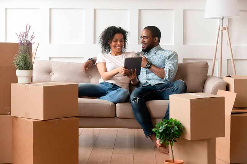 Happy couple sitting on the couch for moving into the new house